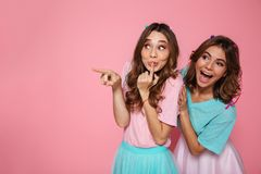 Portrait en gros plan de deux filles heureuses mignonnes se dirigeant avec le doigt, Image libre de droits