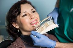 Portrait en gros plan de femme dans le bureau dentaire de clinique Dentiste vérifiant et sélectionnant la couleur des dents denti photo stock
