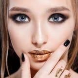 Portrait en gros plan de femme de beauté Le maquillage et la manucure professionnels avec la feuille d'or, smokey observe Couleur photo libre de droits