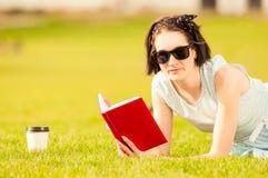 Portrait en gros plan de femme lisant un livre et buvant du café Images libres de droits