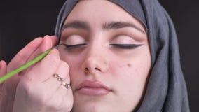 Portrait en gros plan de femme en verres dessinant la flèche noire utilisant la brosse plate mince pour la femme musulmane attira banque de vidéos