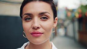 Portrait en gros plan de fille attirante regardant la caméra avec le sourire léger dehors banque de vidéos