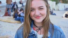 Portrait en gros plan de fille mignonne qui lancent le sourire et la pose in camera, se tenant sur la plage la soirée chaude de r clips vidéos