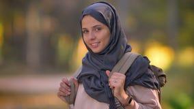 Portrait en gros plan de fille musulmane dans le hijab posant dans la caméra avec le sourire, montrant le sac à dos banque de vidéos
