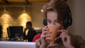Portrait en gros plan de jeune femme aux cheveux courts dans des écouteurs fonctionnant attentivement avec l'ordinateur portable  clips vidéos