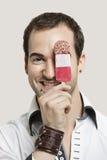 Portrait en gros plan de jeune homme tenant la barre de crème glacée sur le fond gris Photographie stock