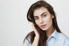 Portrait en gros plan de l'amie sensuelle avec du charme regardant rêveusement l'appareil-photo tout en touchant des cheveux et l Image libre de droits