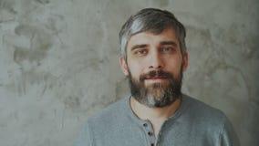 Portrait en gros plan de l'homme d'une cinquantaine d'années barbu souriant et regardant dans l'appareil-photo sur le fond gris banque de vidéos