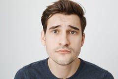 Portrait en gros plan de l'homme européen attirant mignon montrant le regard de chiot avec les sourcils soulevés et le sourire in photos stock
