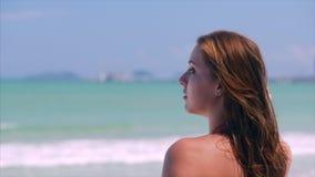 Portrait en gros plan de la belle jeune femme mignonne européenne de brune ou de la fille gaie regardant vers la mer, courant le  banque de vidéos