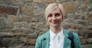 Portrait en gros plan de la blonde parfaite mignonne regardant la caméra souriant dehors banque de vidéos