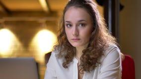 Portrait en gros plan de la jeune femme aux cheveux bouclés travaillant avec l'ordinateur portable aux tours de confusion à la ca banque de vidéos