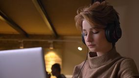 Portrait en gros plan de la jeune femme aux cheveux courts mettant sur ses écouteurs et se déplaçant en musique se reposant le bu banque de vidéos