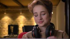 Portrait en gros plan de la jeune femme aux cheveux courts reportant ses écouteurs et observant heureusement dans la caméra dans  clips vidéos