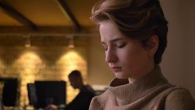 Portrait en gros plan de la jeune femme aux cheveux courts travaillant dans la confusion utilisant l'ordinateur portable dans le  clips vidéos