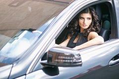 Portrait en gros plan de la jeune femme magnifique de brune conduisant une voiture chère photographie stock libre de droits