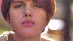 Portrait en gros plan de la jeune fille aux cheveux roses caucasienne fraîche observant attentivement dans la caméra sur le fond  images stock
