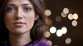 Portrait en gros plan de la jolie fille caucasienne de brune observant attentivement dans la caméra sur le fond brouillé de lumiè photographie stock