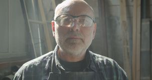 Portrait en gros plan de maître supérieur de menuiserie en verres de sûreté fonctionnant aux montres du bois d'usine dans la camé banque de vidéos
