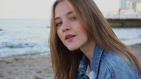 Portrait en gros plan de mouvement lent de la fille mignonne qui sourit et regarde l'appareil-photo, se reposant sur la plage la  clips vidéos