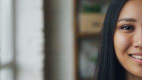 Portrait en gros plan de mouvement lent du demi visage de fille assez asiatique regardant l'appareil-photo et souriant sur le fon banque de vidéos