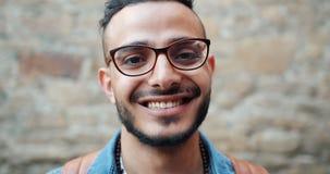 Portrait en gros plan de mouvement lent du type du Moyen-Orient heureux souriant dehors banque de vidéos
