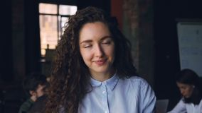 Portrait en gros plan de mouvement lent de l'entrepreneur gai de jeune dame se tenant dans le bureau, regardant l'appareil-photo  banque de vidéos