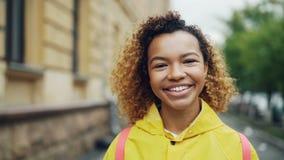 Portrait en gros plan de mouvement lent de la jeune dame de métis mignon souriant et regardant l'appareil-photo avec des bâtiment banque de vidéos