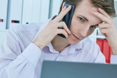 Portrait en gros plan de parler intellectuel au client au téléphone portable dans le bureau sur le lieu de travail par l'ordinate photo stock