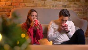 Portrait en gros plan de parler de jeunes amis caucasiens s'asseyant sur le tapis et de boire les boissons chaudes dans Noël banque de vidéos