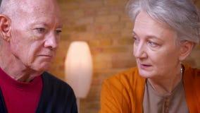 Portrait en gros plan des conjoints caucasiens aux cheveux gris supérieurs parlant les uns avec les autres joyeux clips vidéos