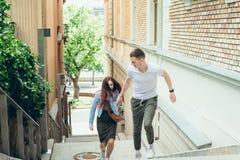 Portrait en gros plan des couples assez affectueux de jeunes tenant des mains tout en allant les escaliers à Budapest étroit photo stock