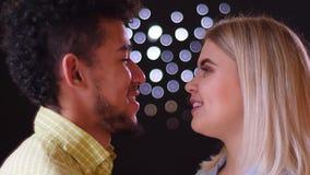 Portrait en gros plan des couples multinationaux observant tendrement dans des yeux sur le fond brouillé de lumières banque de vidéos