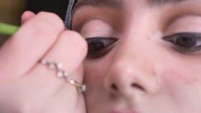 Portrait en gros plan des mains femelles dessinant la flèche noire utilisant la brosse mince pour la femme musulmane dans le hija banque de vidéos