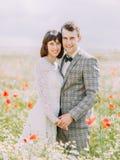 Portrait en gros plan des nouveaux mariés gais tenant des mains et étreignant dans le domaine complètement des fleurs Photographie stock libre de droits