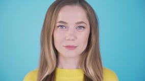 Portrait en gros plan Fille calme sur un fond bleu Fond d'isolement 4 K clips vidéos