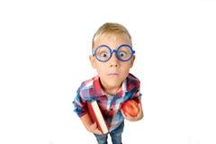 Portrait en gros plan grand-angulaire de garçon un étudiant dans la chemise en verres étreignant le livre et la pomme dans des ma image stock