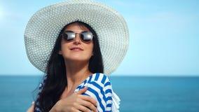 Portrait en gros plan moyen de femme de voyage de beauté dans le chapeau blanc et des lunettes de soleil posant au fond de mer clips vidéos