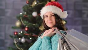 Portrait en gros plan moyen de la femme adorable de sourire tenant peu le paquet de cadeau près de l'arbre de Noël clips vidéos