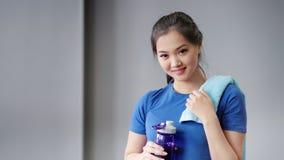 Portrait en gros plan moyen de la femme asiatique de sourire fatiguée après eau potable de séance d'entraînement de bouteille banque de vidéos
