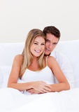 Portrait of an enamored couple sitting on bed. At home royalty free stock image