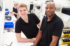 Portrait Of Engineer In Factory With Apprentice At Bench Stock Photo