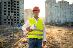 Portrait of engineer posing with blueprints against building sit Stock Image
