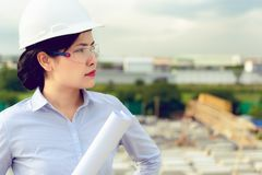 Portrait of engineer woman is holding paperwork at construction royalty free stock image