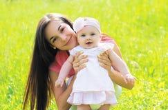 Portrait ensoleillé de jeune mère heureuse avec le bébé sur l'herbe photos libres de droits