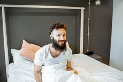 Man waking up in the bed. Portrait of enthusiastic bearded man, waking up in the bed, feeling good in the morning stock photography
