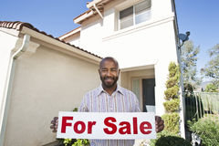Portrait Of An Estate Agent Holding ~For Sale~ Sign. Portrait of an African American estate agent holding ~For Sale~ sign against house stock photo