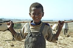 Portrait Ethiopian Oromo boy with stick. Ethiopia, Oromia, village Chancho Gaba Robi: This child is standing on the farmland of his father, who is plowing in the Royalty Free Stock Photo