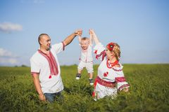 Portrait of ethnic ukrainian family. Wearing traditional white clothes. Father, mother and little baby having fun outside at summer sunny field. Horizontal stock image