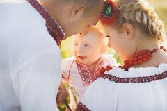 Portrait of ethnic ukrainian family. Wearing traditional white clothes. Father, mother and little baby having fun outside at summer sunny field. Horizontal royalty free stock photo